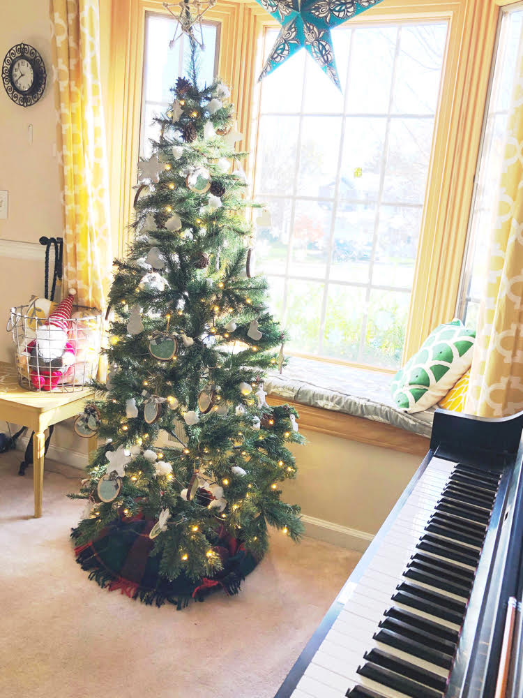 a rustic and minimal realistic looking artificial christmas tree with homemade ornaments by a piano