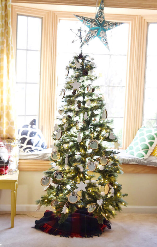 A rustic artificial / faux Christmas tree decorated with homemade ornaments