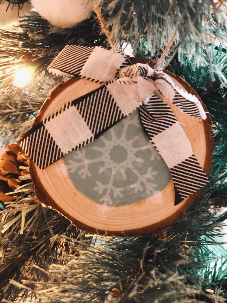 rustic wood slice snowflake ornament hung in a Chrstmas tree.