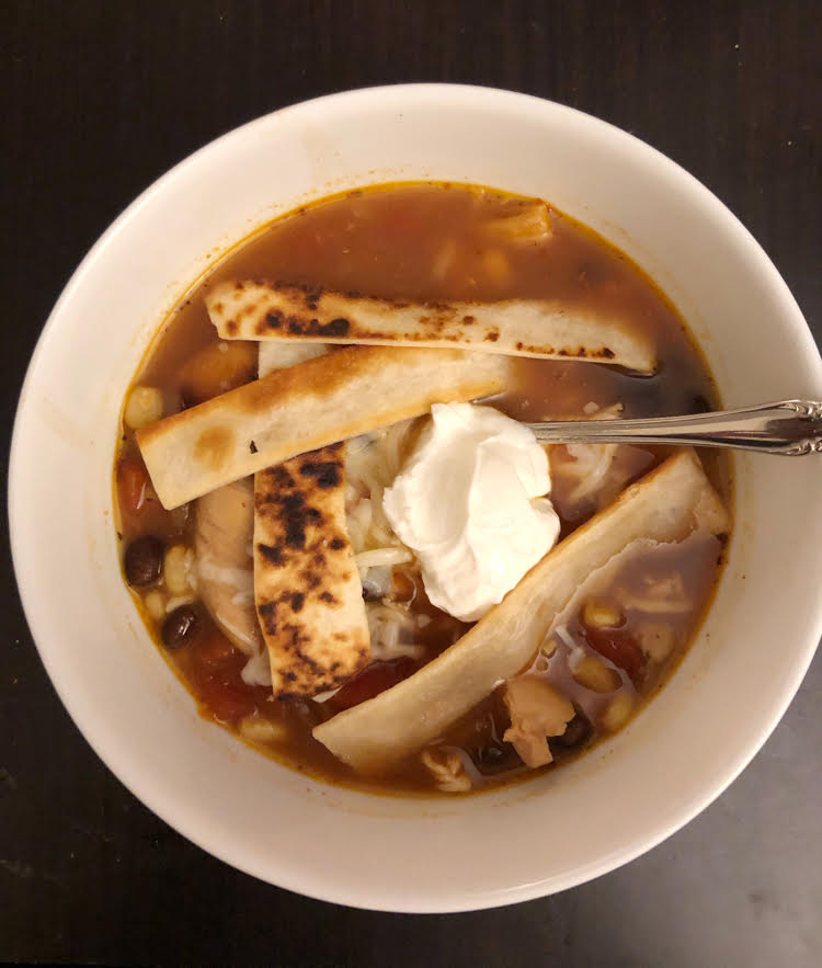 a delicious bowl of homemade chicken tortilla soup topped with sour cream