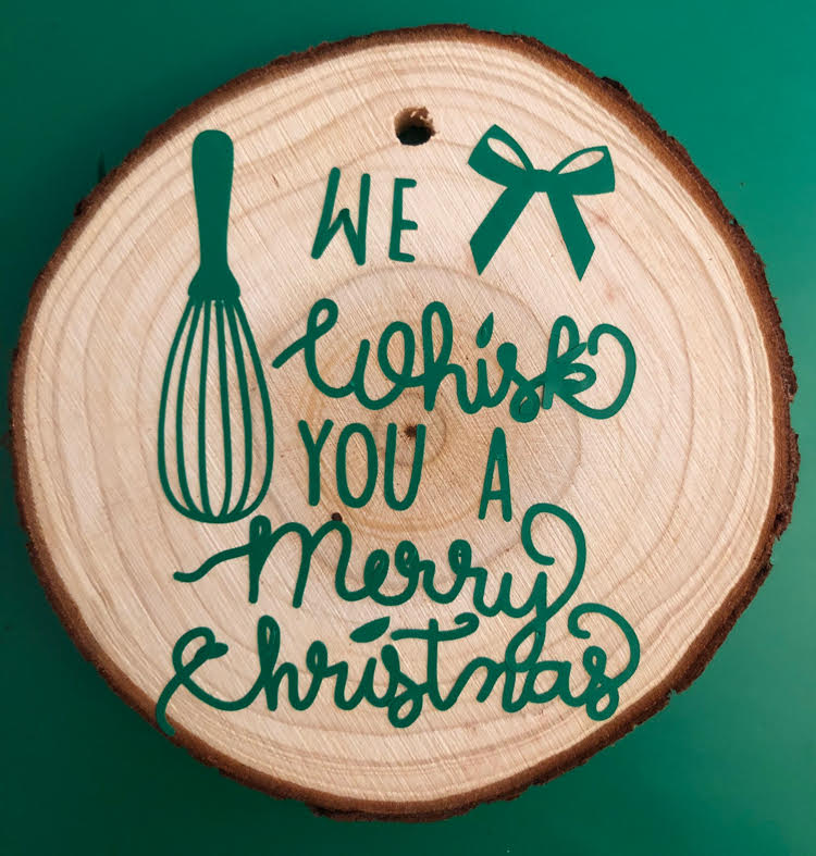 """a homemade """"We Whisk You a Merry Christmas"""" wood slice ornament"""