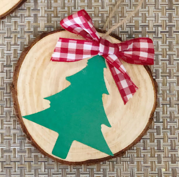 a handmade wood slice ornament decorated with a vinyl Christmas tree and a red and white buffalo plaid ornament