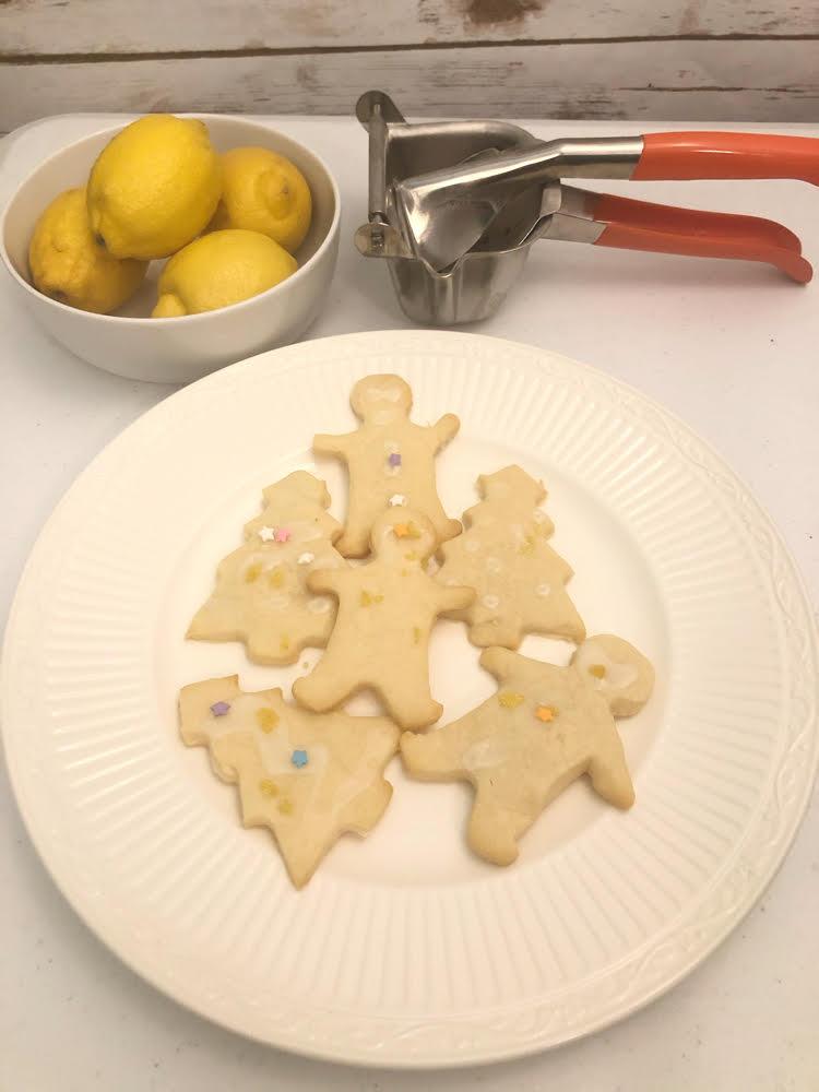 cut out lemon shortbread cookies and a manual citrus/lemon juicer and a bowl of lemons