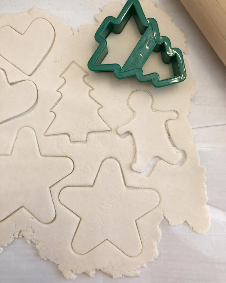 cutting dough with cookie cutters to make salt dough ornaments for Christmas and the holidays