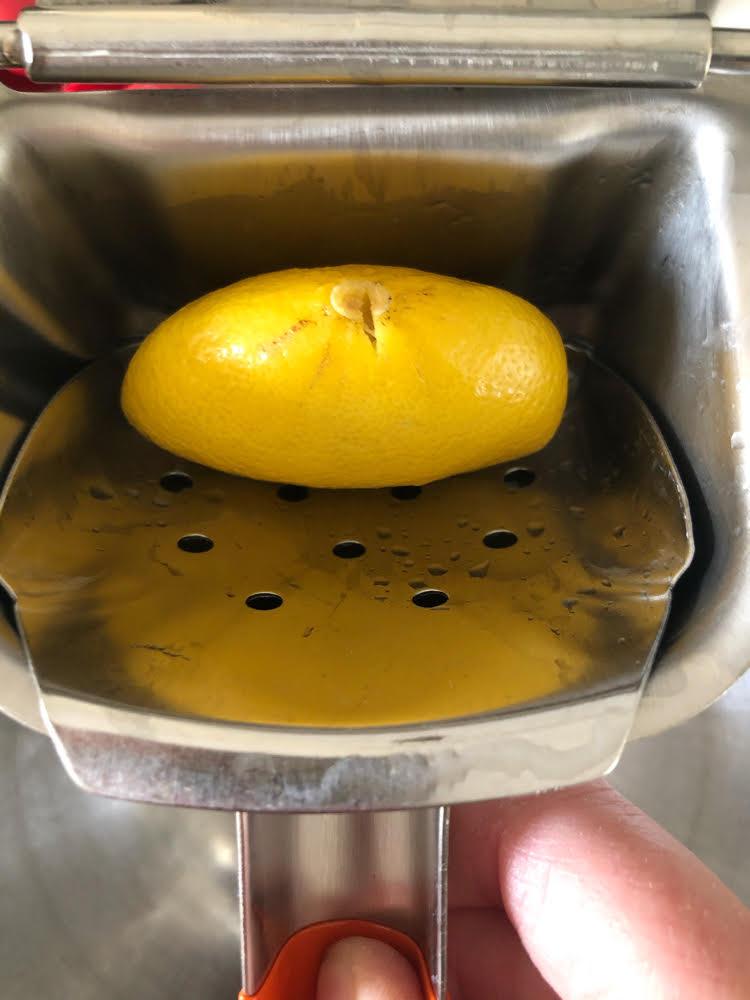 manual citrus and lemon juicer with a squeezed lemon inside