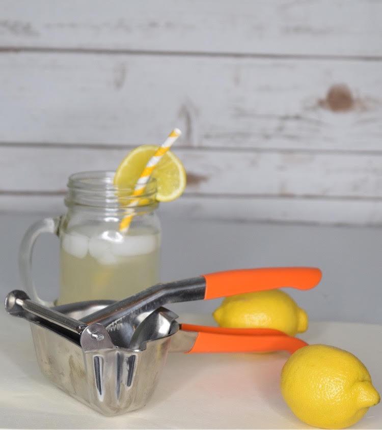 stainless steel citrus juicer, lemons and mason jar glass of lemonade