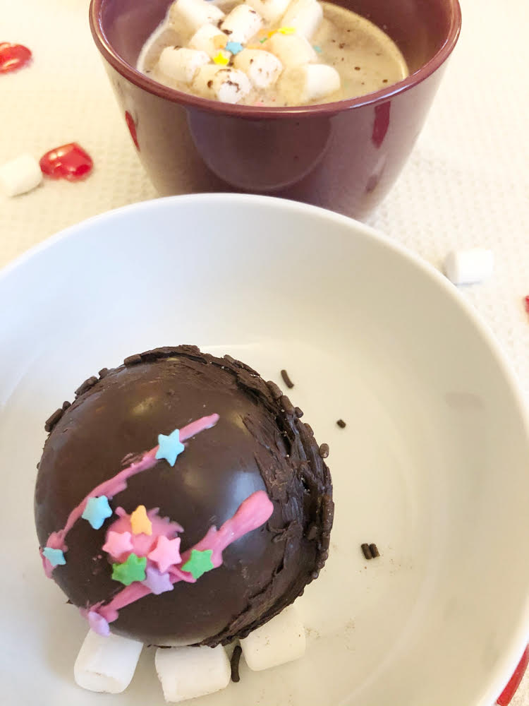 DIY mocha hot cocoa bomb with a cup of hot chocolate with mini marshmallows