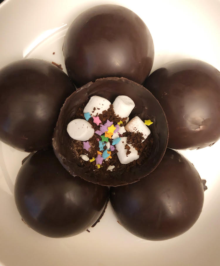 ingredients for mocha hot cocoa bombs: chocolate set in half-sphere molds and filled with hot cocoa mix, instant coffee, sprinkles and mini marshmallows