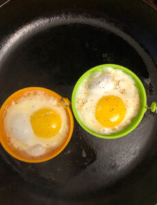 a yellow and a green silicone food grade egg and pancake ring and two fried eggs