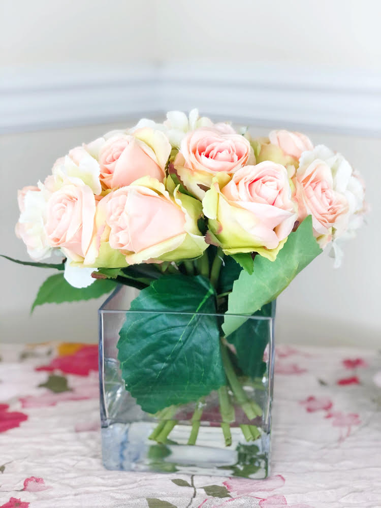 artificial bouquet of pink roses and hygrangea in a square vase