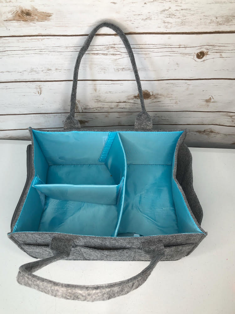 The felt Mimmo Caddy by Mollie Ollie has removable dividers to make compartments within the caddy.