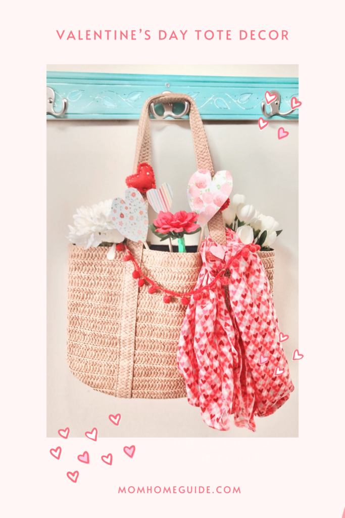 a straw tote filled with paper and felt hearts and decorated with a hearts scarf and pom pom fringe