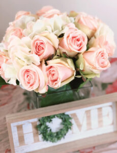 Sweet glass vase filled with faux roses and hydrangea with a farmhouse home sign