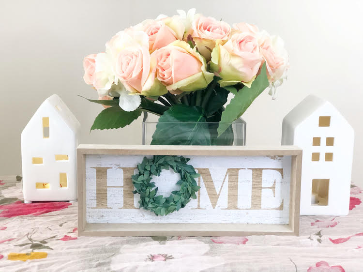 Sweet artificial rose and hydrangea bouquet on a table with white ceramic mini houses and a farmhouse home sign
