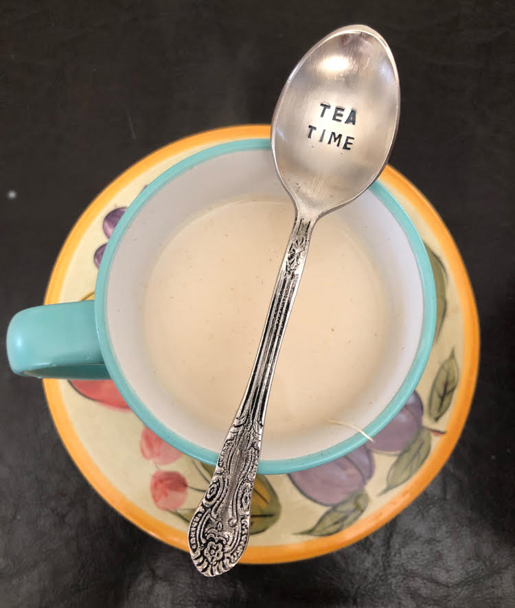 tea time engraved spoon placed across a mint green tea cup
