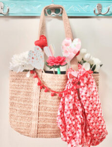 A pretty straw tote decorated for Valentine's Day with a pom pom garland, heart scarf, faux flowers and felt and paper hearts.