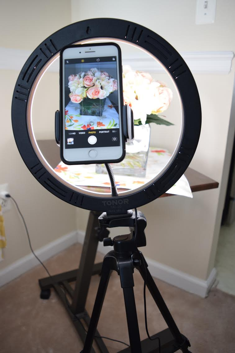 A mini photo studio setup with an iphone, a TONOR 12 inch selfied ring light with tripod stand, smartphone holder and Bluetooth Remote Shutter, and a Seville mobile laptop desk cart