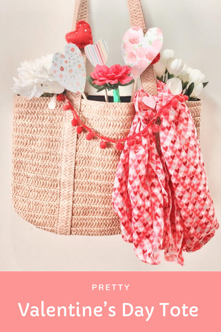Valentine's Day straw bag with paper and felt hearts, a mini pom pom garland, faux flowers and a Valentine's Day scarf