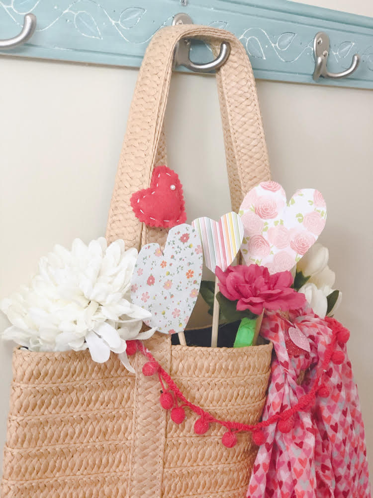 A straw tote decorate with faux flowers, felt and paper hearts, a heart scarf and a pom pom garland.