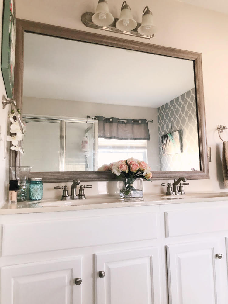 a bathroom mirror framed with a MIrrorChic frame; a painted bathroom vanity