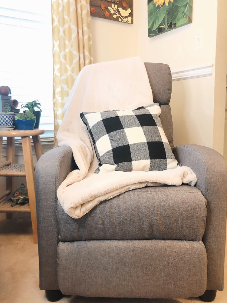 beautiful gray recliner tray with a white fuzzy blanket and a black and white buffalo check pilow