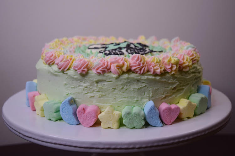 cake decorated with green icing, rainbow piped stars and Lucky Charms marshmallows