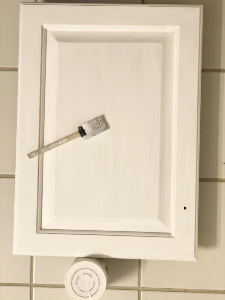 using a foam paint brush to paint a bathroom cabinet