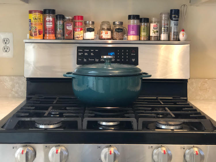 stoveshelf, a handy magnetic shelf for the top of a stove, and a green Dutch oven on a rangetop