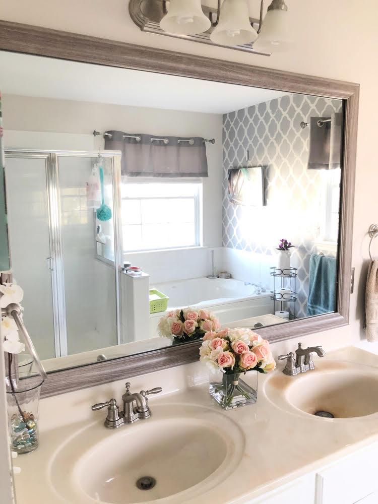 a bathroom mirror framed with a MirrorChic frame