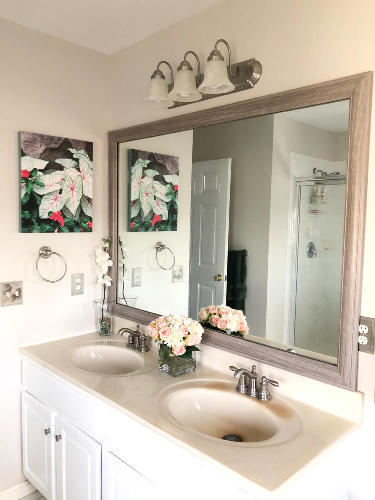 a builder grade bathroom mirror framed with a custom mirror frame from MirrorChic.com