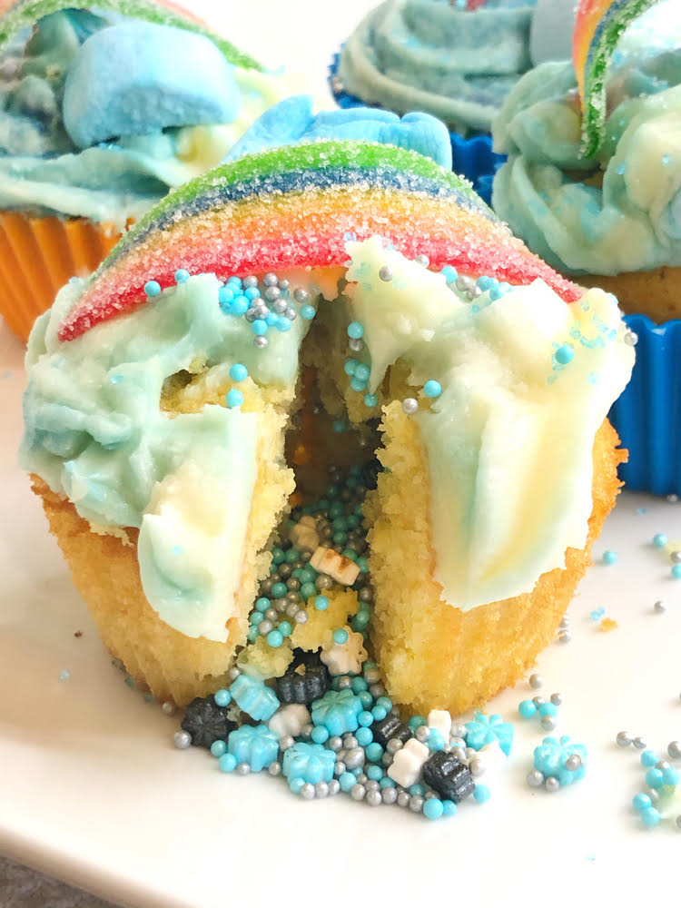 cupcake with sprinkles pouring out of its center