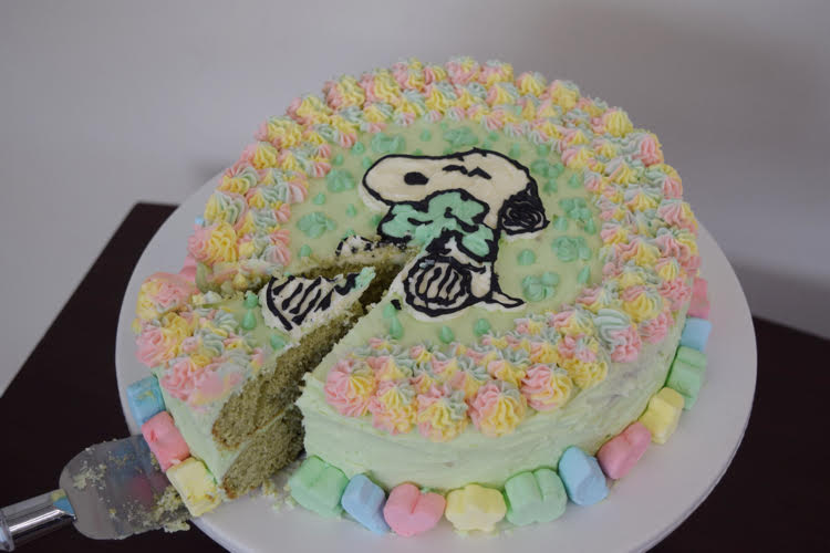 A green frosted cake with rainbow piped stars and a Snoopy and shamrock design on the top. The cake is lined with Lucky Charms marshmallows