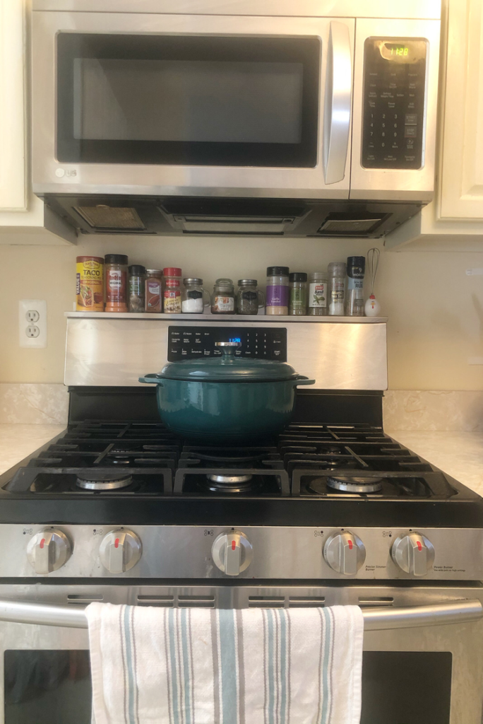 a stainless steel stove topped with Stoveshelf, an inexpensive magnetic shelf that can be placed on top of a stove