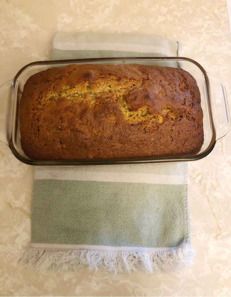 healthy banana bread loaf made with applesauce instead of bread in a glass pyrex baking dish