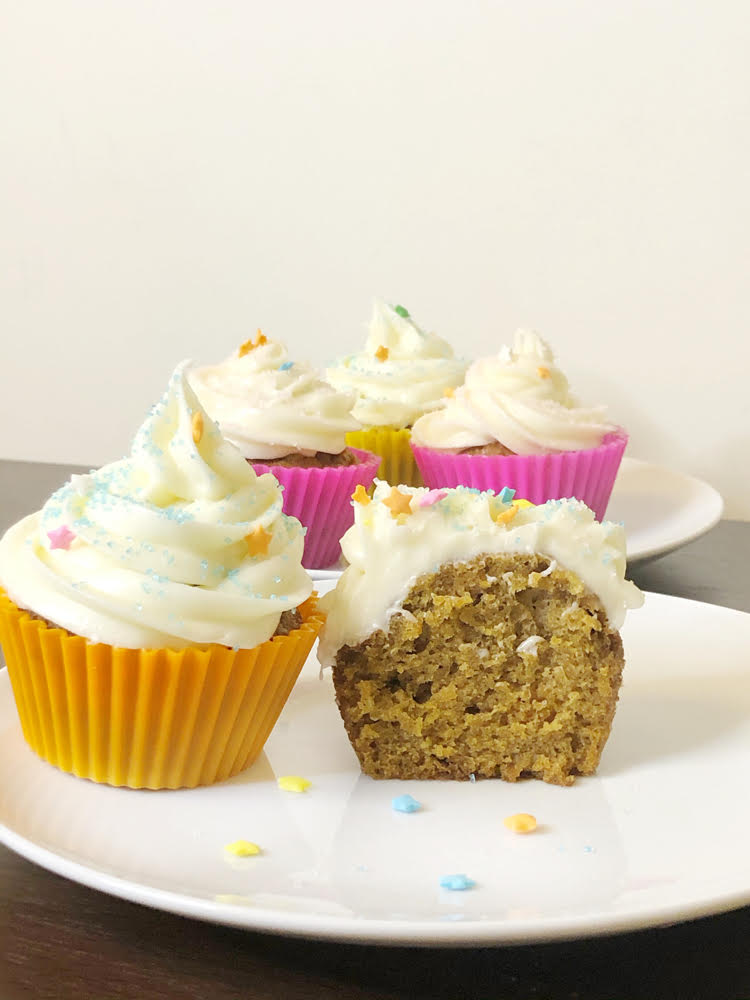 carrot cupcakes with cream cheese icing in colorful silicone cupcake wrappers
