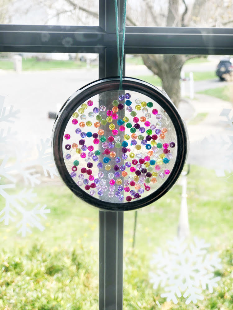 a pretty DIY suncatcher made with a mason jar ring, beads and iridescent beads