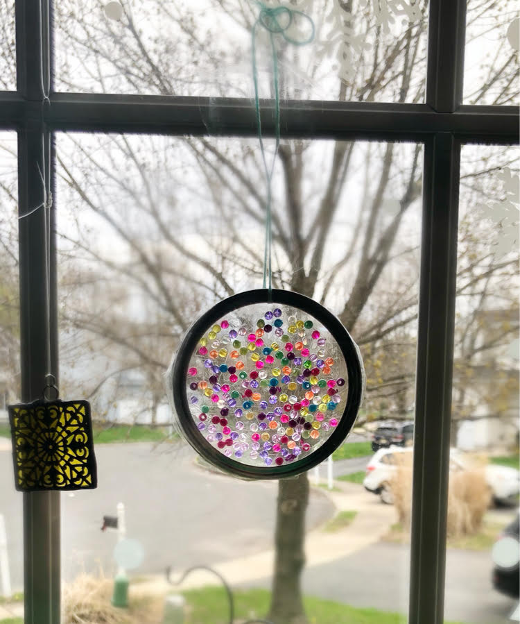 a beautiful suncatcher made with a mason jar ring, iridescent beads and Duck tape.