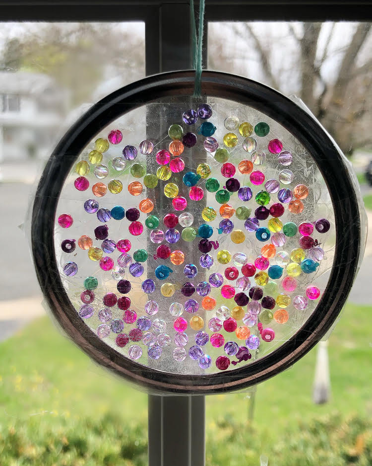 a DIY suncatcher made with a mason jar ring and small colorful iridescent beads and Duck tape