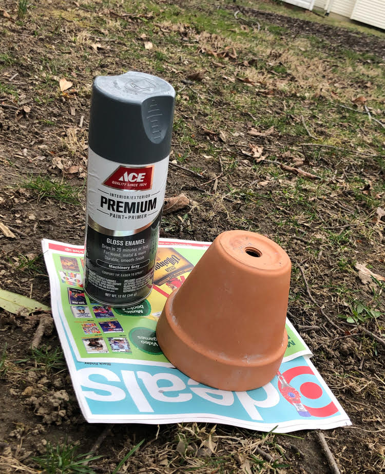 gray spray paint can and a terra cotta pot