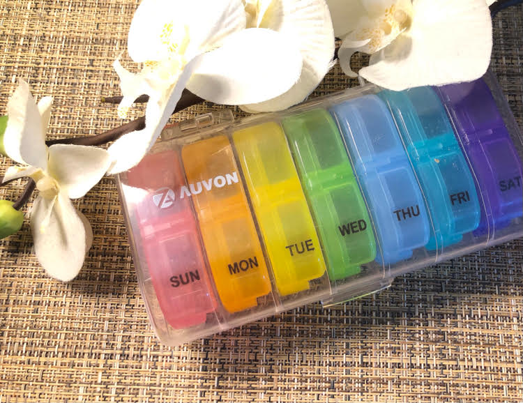 colorful daily pill organizer with separate daily pill containers with day and night pill sections