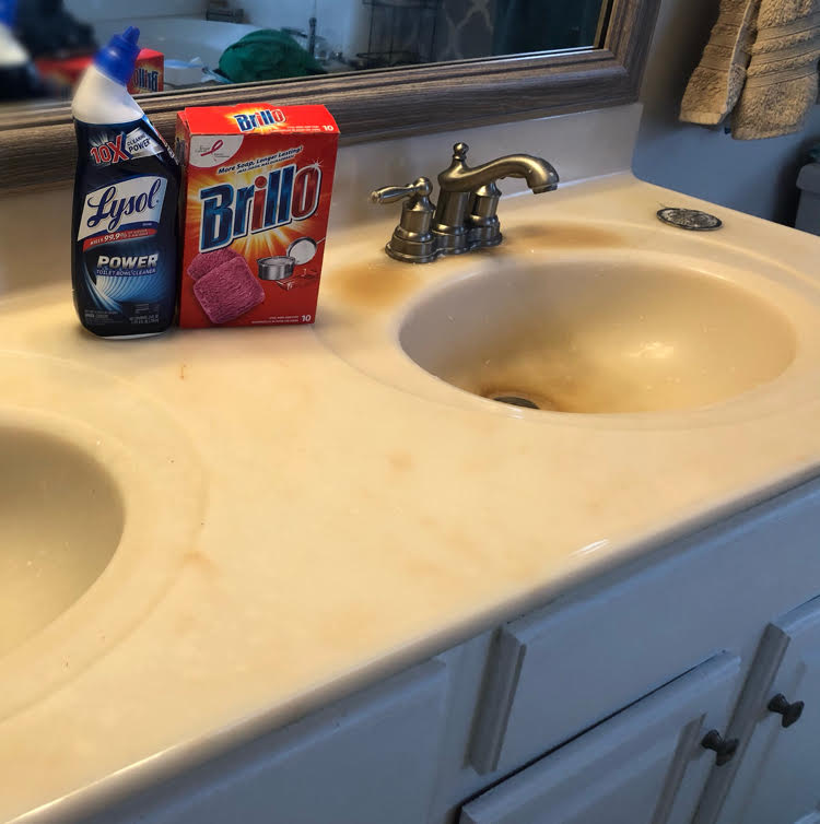 A cultured marble countertop with double sinks before updating them.