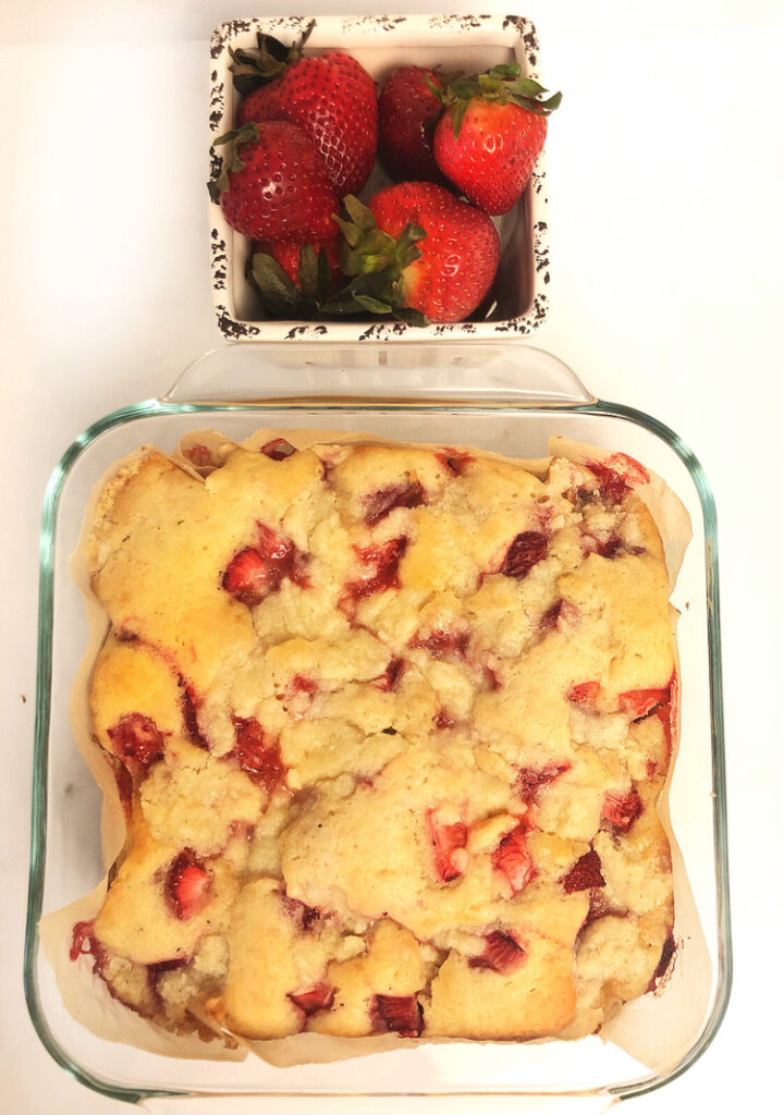 fresh strawberry coffee cake and a ceramic container filled with strawberries