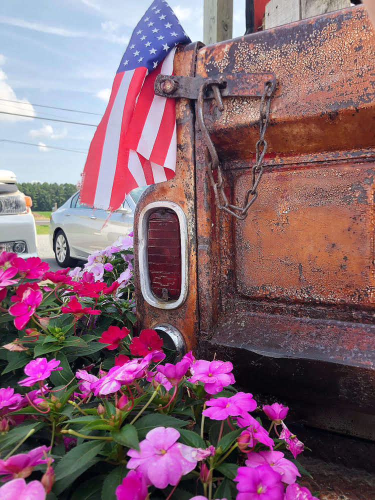 vintage pickup truck with flowers and American flag